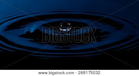 Water Droplet With Ripples Blue And Black.