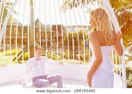 Beautiful Blonde Bride In White Wedding Dress And The Groom In A White Gazebo At The Hotel. Tropical