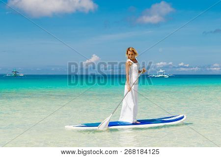 Happy Beautiful Young Girl In A White Dress With Paddle Board On A Tropical Beach. Blue Sea In The B