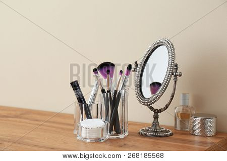 Organizer With Cosmetic Products For Makeup And Mirror On Table Against Light Wall