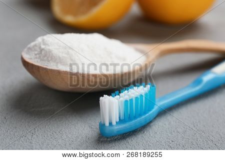 Spoon With Baking Soda And Toothbrush On Gray Table