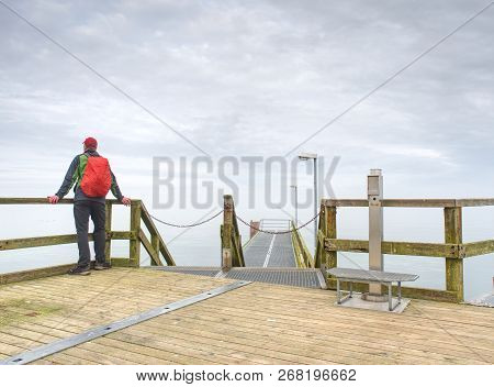 Tourist At Dusk On The Docks Bridge And Looks Afar. Pensive Boy In Trekking Suit  On A Wooden Pier A