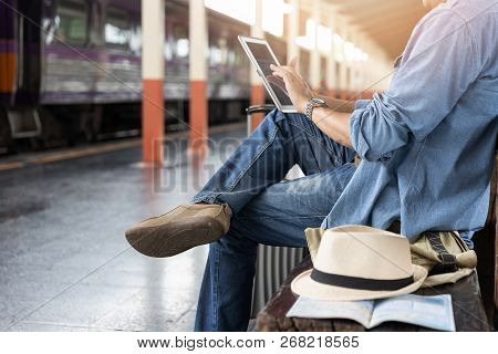 Asian Traveler Man Use Tablet To Buy Train Ticket Online At Chiang Mai Train Station, Thailand