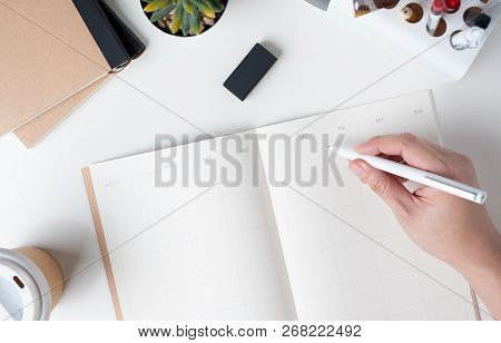 Top View Of Hand Writing On Open Calendar Planner For Business Resolution With Modern Office Station