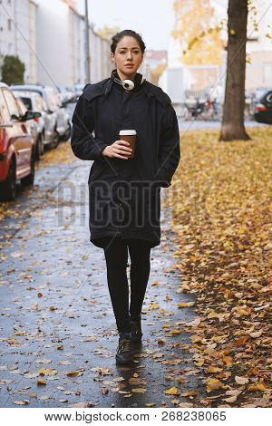 Young Woman Walking Down City Street Alone On A Wet Cold Autumn Day Wearing Parka Coat With Headphon