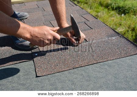 Roofer Installing Asphalt Shingles  On House Construction Roof Corner With Hammer And Nails. Roofing