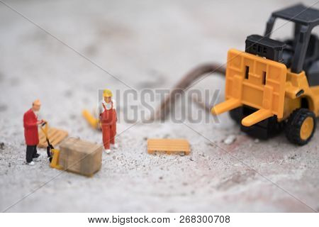 Miniature Warehouse Workers Forklift Carrying Goods Box To Semi Truck With Trailer. Logistics Wareho
