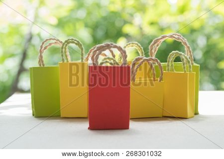 Miniature Paper Shopping Bag With Nature Green Background. Online Shopping And Delivery Service Conc