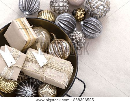 From Above Shot Of Arranged Shiny Balls In Bowl With Wrapped Gift Boxes For Christmas Holiday.