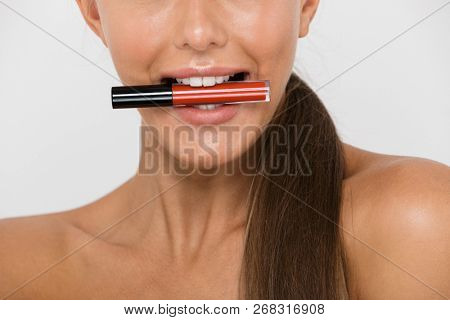 Close up of a pretty young topless woman isolated over white background, holding lip gloss with her teeth poster
