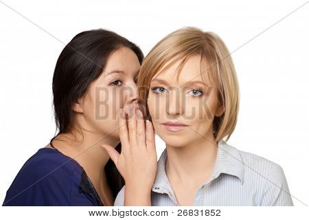 Close-up portrait of two pretty young women gossiping, over white background