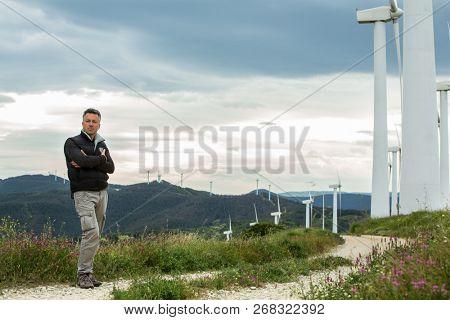 Man's portrait outdoor against blue sky with wind turbine. Windmill generators. Wind power generators.