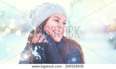 Winter girl portrait. Beauty Joyful Model Girl touching her face skin and laughing, having fun in winter park. Beautiful young woman laughing outdoors. Enjoying nature, wintertime