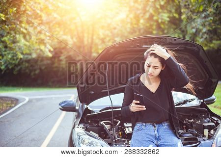 Woman Using Mobile Phone While Looking At Broken Down Car On Road.