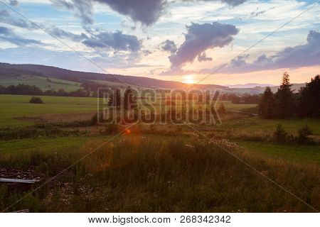 Summer Landscape With Sunset. Cloudy Sky, Trees And Grass Field