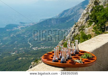 Tray With Little Wine Bottles And Parsley In Front Of Hills And Rocks Of Biokovo Mountain Range And