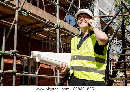 Male Construction Worker, Foreman Or Architect On Construction Site Talking On His Cell Phone And Ho