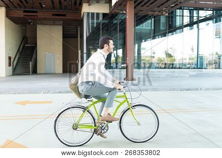 Side View Of Male Executive Commuting On Cycle While Going To Work