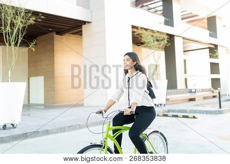 Female Cyclist Smiling While Commuting To Work In City