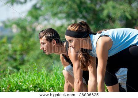 Casal jovem da aptidão do homem e da mulher, pronta para começar a correr