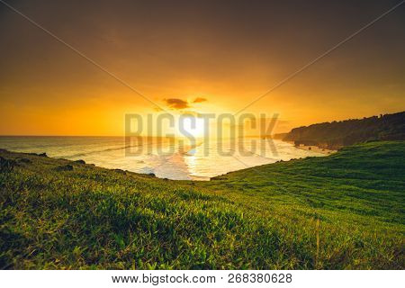 Sunset sun rays, green meadow, ocean. Indonesia. Stunning panoramic view. The bright colorful sunset over the Indian ocean and exotic Sumba island. The splash of orange, yellow and green colors.