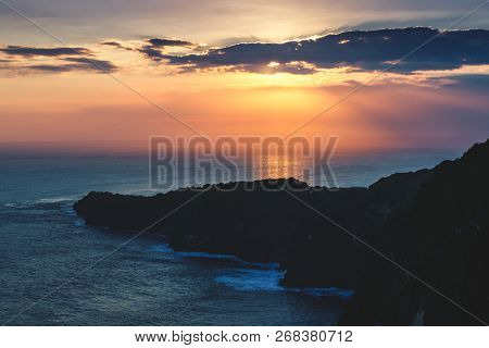 Sunset cloudy sky. Ocean, cliff Bali island. background. Amazing panoramic view the Indian ocean and the cliffs under the bright sunset lights. Beauty of wild untouched nature.