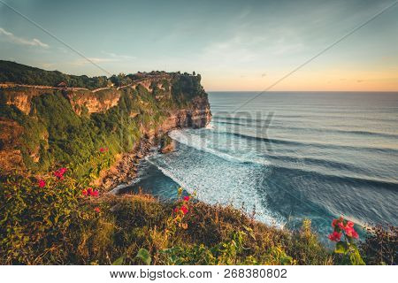 Overview panorama ocean shore, cliff. Sunset. Bali. Overwhelmed scene the flower and green-capped vertical cliff over the Indian ocean. South of Bali island, Pura Luhur Uluwatu Temple. Indonesia.
