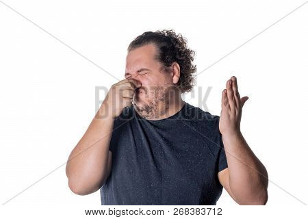 A young man holds or pinches his nose shut because of a stinky smell or odor. Isolated on a white background poster