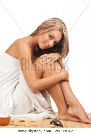 Portrait of young beautiful spa woman sitting on bamboo mat at spa salon