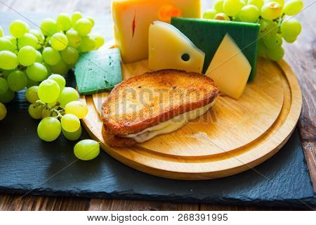 Hot Grilled Or Fried Sandwich With Cheese And Green Grapes On Black Slate Cheeseboard On Wooden Tabl