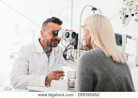 Optician examining woman's eyes with a machine. Eyesight care, doctor's appointment.