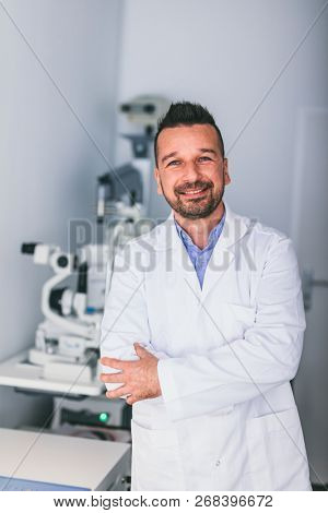 Doctor standing confident in his office, exam room. Optician