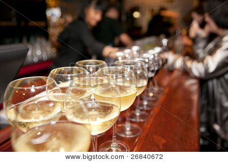 Wineglasses on bar counter with blurred crowd in background
