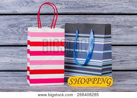 Shopping Bags On Wooden Background. Paper Shopping Packets And Color Card With Inscription Shopping.