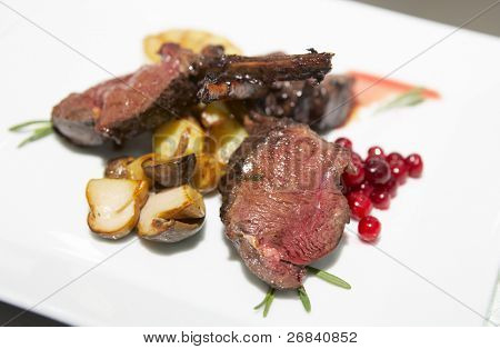 Rare kooked steak with fried mushrooms and currant topping