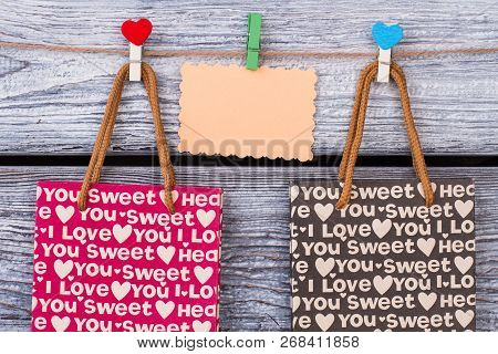Valentine Holiday Gift Bags. Shopping Bags With I Love You Printing And Blank Paper Card On Wooden B