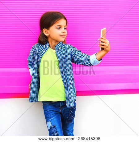 Smiling Child Taking Selfie By Smartphone In City On Colorful Wall Background