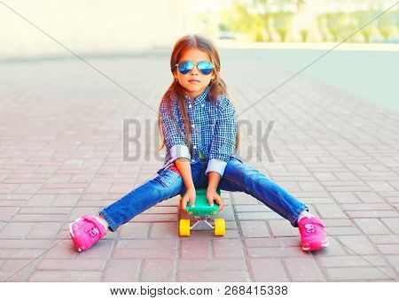 Stylish Little Girl Sitting On Skateboard On City Street