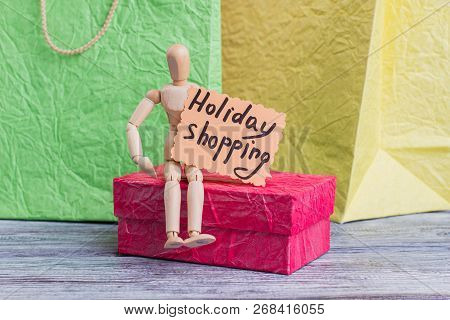 Holiday Shopping Concept. Wooden Puppet Sitting On Gift Box And Holding Card With Inscription Holida