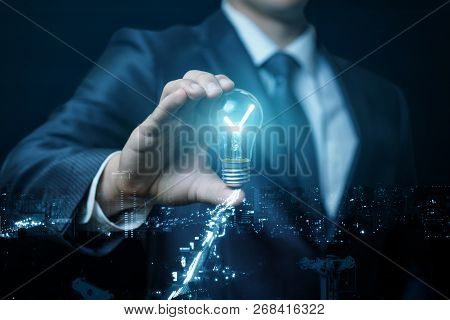 A Businessman Is Holding A Burning Lightbulb Between His Fingers At The Dark Background. The Concept