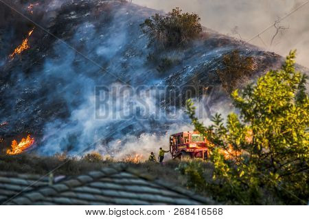 Two Firefighters Next To Red Bulldozer With Burning Hillside In Background During California Brushfi