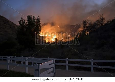 California Fire Burns Hillside Behind Suburban Neighborhood Park With Fence In Foreground.