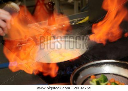 Chef is making flambe sauce on restaurant kitchen, motion blur