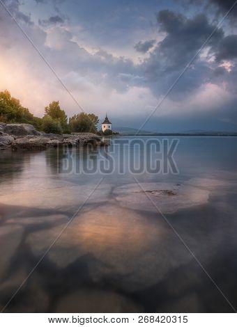 Church By Liptovska Mara Lake At Sunset In Slovakia