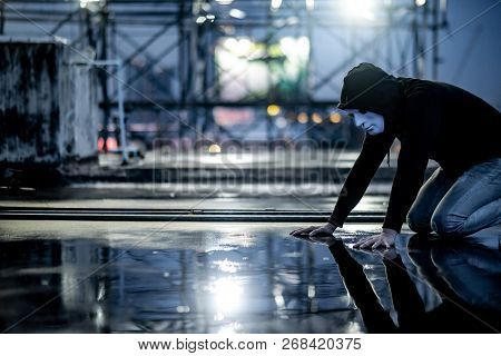 Reflection Of Mystery Hoodie Man In White Mask Feeling Guilty Looking His Face On Wet Floor While Ra