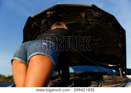 Image Of Back Of Young Girl In Short Shorts Mending Black Car In Summer Day On Street