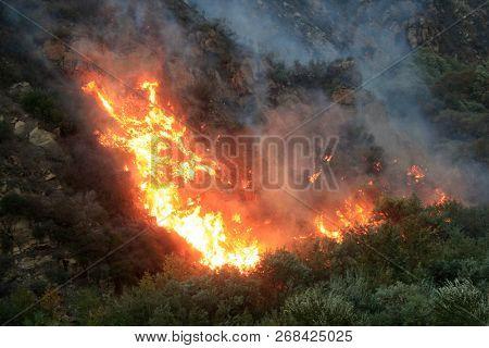 MALIBU - NOV 11: Flames are seen in Malibu canyon along the road during the wildfire in Malibu, CA on November 11, 2018