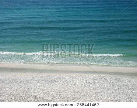 The Waves Gently Roll Against The White Sands Of The Emerald Coast In Destin, Florida.