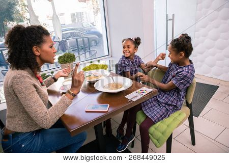 Dark-haired mother telling her girls to behave good sitting in cafeteria poster