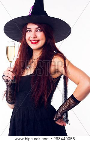 Portrait of witch with wine glass with wine in black dress and hat